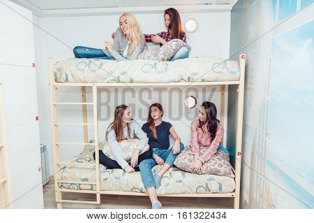 Beautiful girls sitting on a bed in hostel talk and have fun.