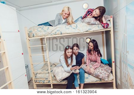 Beautiful girls sitting on a bed in hostel talk and have fun. Using smartphone.