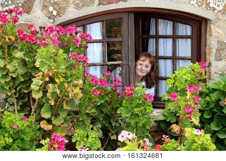 Young beautiful ginger-haired girl looking out of the window