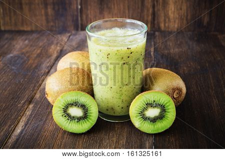 Kiwi green smoothie in glass on wooden background selective focus toned horizontal