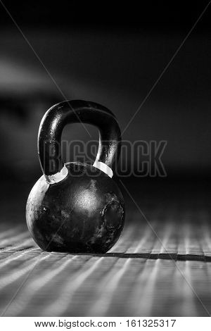 Close up view of a kettlebell on the floor in a dark gym with edgy lighting.
