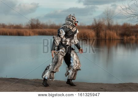 Man wolf werewolf runs near the lake.
