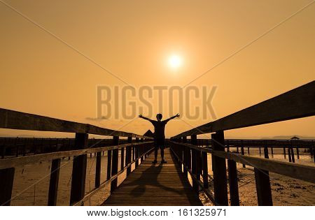 Silhouette happy free man on wood bridge with sunny Relaxing by open arm independent.