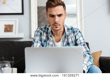 Image of concentrated bristle man dressed in shirt in a cage print sitting on sofa in home and using laptop computer. Looking at laptop.