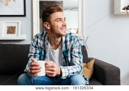 Photo of happy young bristle man dressed in shirt in a cage print sitting on sofa in home and holding cup of tea.