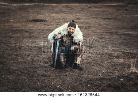 Formidable man with a sword stood on one knee in the field.