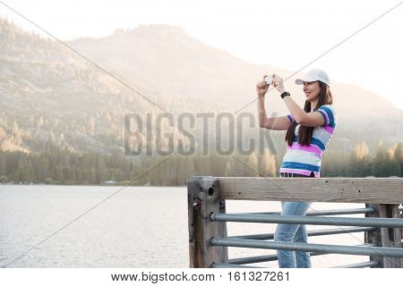Young woman in hat taking picture of a beautiful mountain landscape with mobile phone while standing on wooden pier
