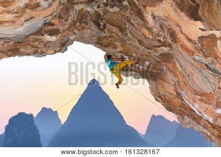 Strong Male Rock Climber ascending dangerous rocky Roof karst Mountains in China on Luminous Sunrise Background