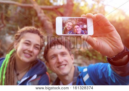 Two Hikers Handsome Man and Cute Girl with Dreadlocks Hair Style smiling taking self Portrait Photo with smart phone on Hike in Spring Time Forest