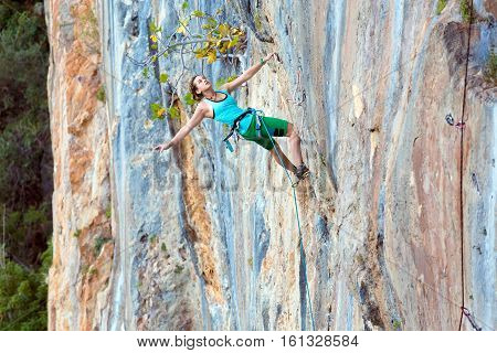 Extreme Sport Athlete hanging on vertical natural Wall stretching her Hand to reach next Hold bright orange blue stone color