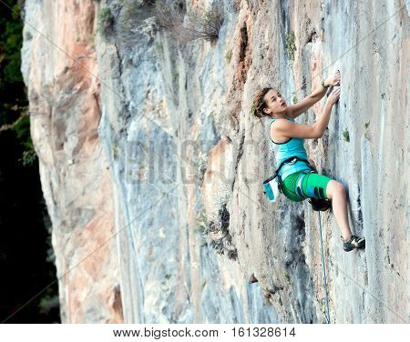 Portrait of Junior Female Athlete tenaciously hanging on colorful blue orange rocky Wall