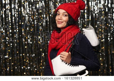 Smiling young woman in red winter hat and scarf carrying a pair of ice skates over glittery background