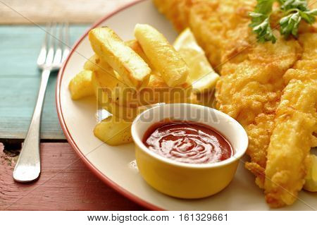 Deep fried battered fish on a plate with chips close up
