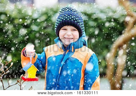 Little kid boy feeding birds in winter. Cute happy preschool child hanging colorful selfmade bird house on tree on frosty cold day. Preschooler in colorful wam clothes. Nature empathy with animals.