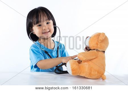 Happy Asian Chinese Little Doctor Girl Examine Teddy Bear