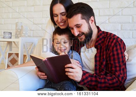 Close-up of happy family, spending time together. Loving wife and mum embracing her dearest while spending time when reading a book. The concept of togetherness