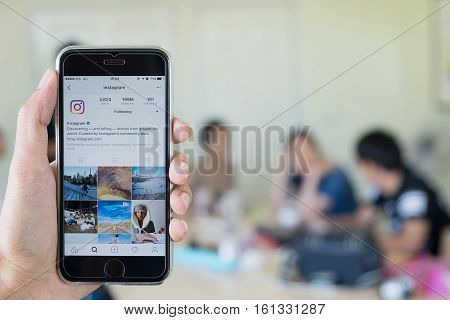 CHIANG MAI THAILAND - NOV 20 2016: A man holds Apple iPhone with Instagram application on the screen. Instagram is a photo-sharing app for smartphones. with people meeting background