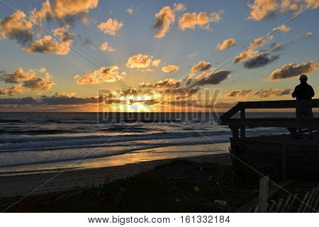 Silhouette of person observing sunrise at the beach Florida, USA.