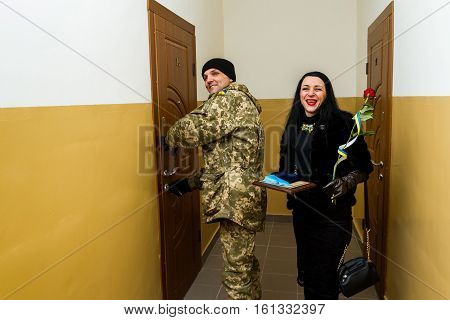 Chop Ukraine - December 6 2016: A soldier of the Armed Forces of Ukraine with his wife opens the door to a new apartment after receiving the keys. On this day in Chop 23rd soldiers who served in the ATO it was handed the keys to new apartments.