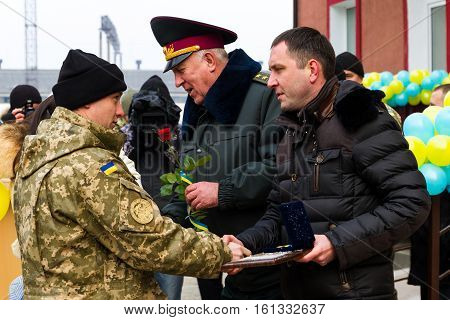 Chop Ukraine - December 6 2016: A soldier of the Armed Forces of Ukraine (L) receives the keys to a new apartment. On this day in Chop 23rd soldiers who served in the ATO it was handed the keys to new apartments.