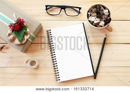 Business, work day, Christmas or New Year concept : Workspace desk with notebook, pencil, pine cones in tea wooden cup, eye glasses, gift box and ribbon on wooden background