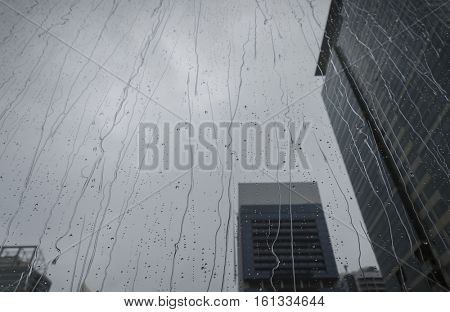 Rain water sliding on the window pane of an office tower.