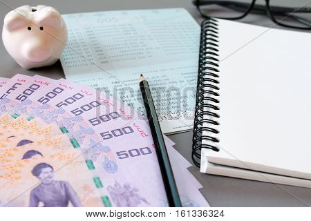 Business, finance, investment or savings background concept : Blank notebook, pencil, savings account passbook, eye glasses, Thai money and piggy bank on gray background