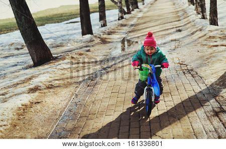 little girl riding bike in winter or spring, kids seasonal activities
