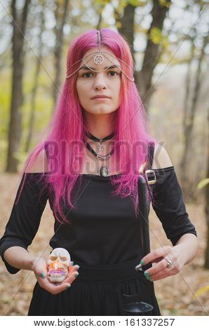 Young witch with pink hair performing a magical ritual with a black dark candle faded colors selected focus