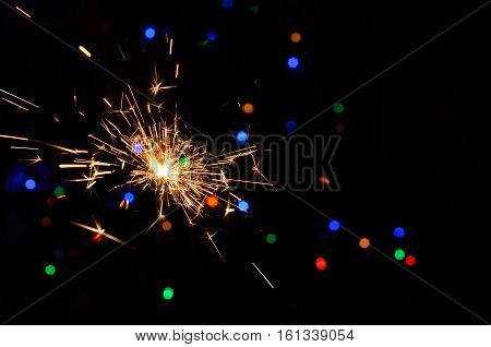 Sparkler on bokeh background. Christmas sparkler. Christmas background.