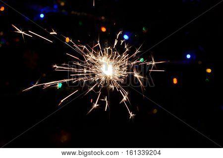 Blurred background. Sparkler on bokeh background. Christmas sparkler.