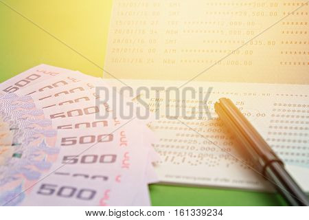Business, finance, investment or savings concept : Savings account passbook, Thai money and pen on green background