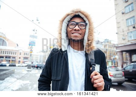 Picture of african cheerful man walking on the street. Looking aside.