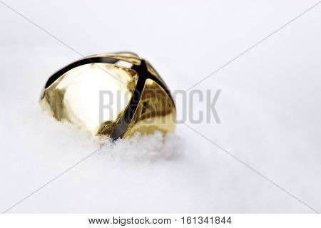 Beautiful golden jingle bell nestled in freshly fallen snow with room for copy.