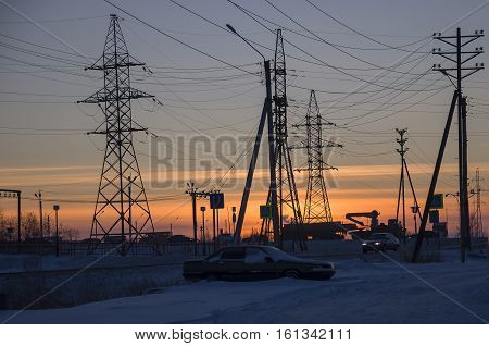 Winter bright sunset with many electric poles and wires. North. At the polar circle