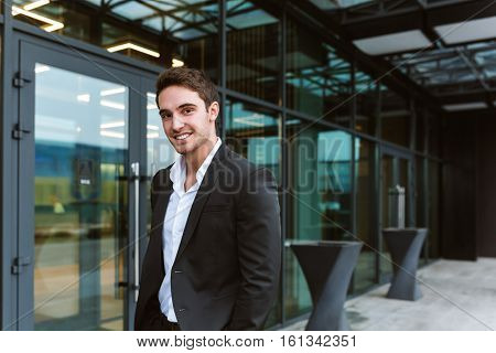 Smiling Business man in suit standing near the office and looking at camera