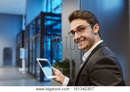 Back view of Smiling Business man in suit and glasses with laptop computer looking at camera in office
