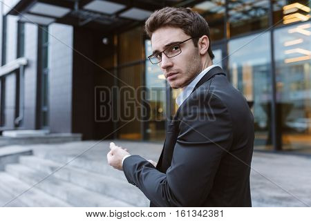 Business man in suit and glasses standing sideways and looking at camera near the office