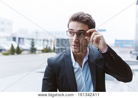 Cool Business man in suit and glasses standing on the street, holding his glasses and looking away