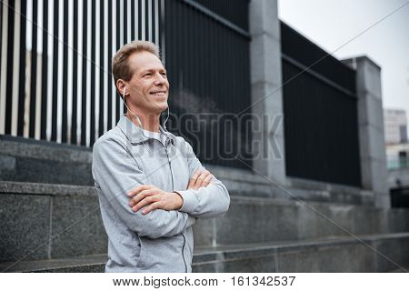 Smiling Runner in gray sportswear and headphone standing with arms crossed on the street. Side view