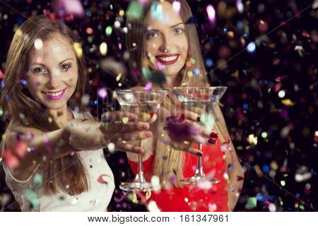 Two beautiful young women having fun at a party holding martini glasses and making a toast. Focus on the girl on the left