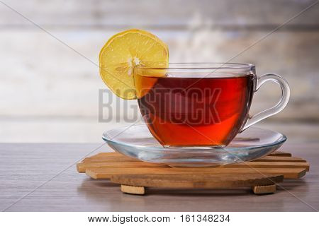Hot cup of tea with a lemon on the table.