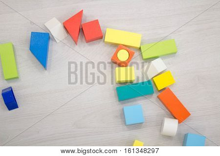 Scattered heap of toy colored wooden bricks toy cubes, isolated on white