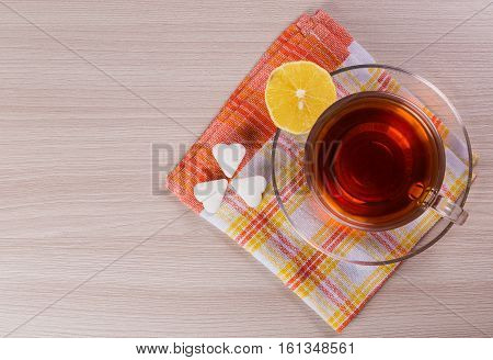 Hot cup of tea with a lemon on the table pieces and sugar.