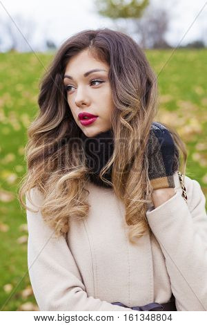 Portrait of a young beautiful brunette woman in beige coat posing on a background of autumn park