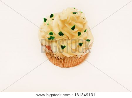 Birthday vanilla cupcake muffin with butter cream icing isolated on white background. Sweet dessert with small fir-trees sprinkles on top