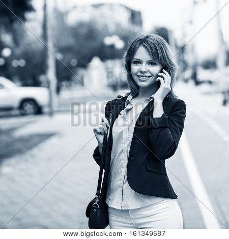 Young businesswoman speak on the phone walking on the street
