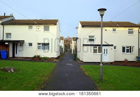 Bracknell,England - December 09, 2016: Footpath between houses in the early morning light under a cloudy sky on a housing estate in Bracknell, England
