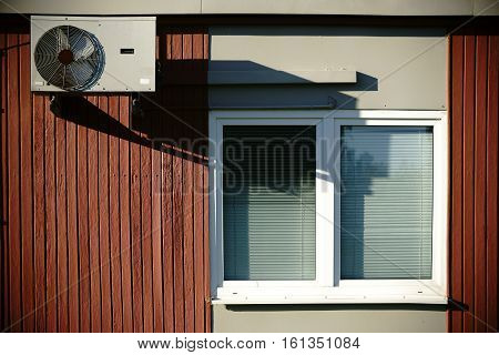 A wooden barack with wooden walls is equipped with a window and fan.
