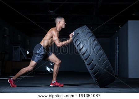 Personal trainer flipping a tyre in a dark gym while instructing a female fitness model how to do the excersise.